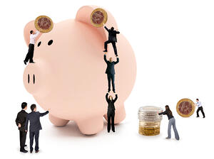 Business people putting savings on a piggy bank - isolated