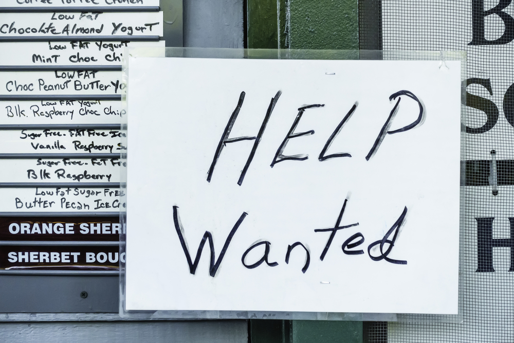 Laminated handwritten Help Wanted sign in window of ice cream and yogurt shop in tourist town-1