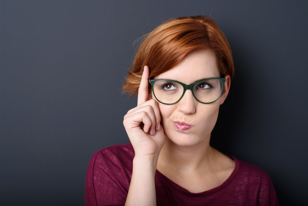 Nerdy scholastic young woman wearing geeky glasses standing thinking with her finger raised and a grimace of concentration in a humorous stereotypical depiction, over a dark background with copyspace